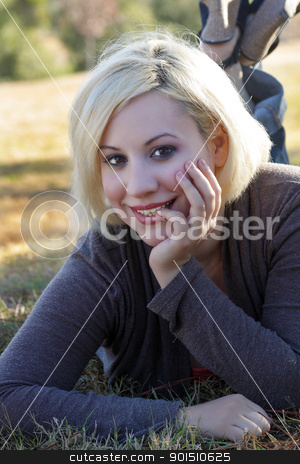 Beautiful Blonde Outdoors (5) stock photo, A close-up of a beautiful blonde with a captivating smile, lying in the grass, backlit by the early-morning sun. by Carl Stewart