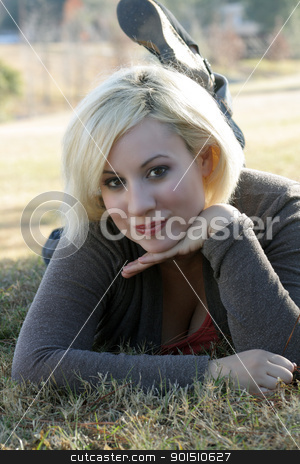 Beautiful Blonde Outdoors (7) stock photo, A close-up of a beautiful blonde with a captivating smile, lying in the grass, backlit by the early-morning sun. by Carl Stewart