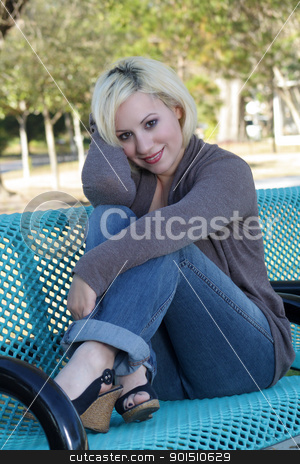 Beautiful Casual Blonde on a Park Bench (2) stock photo, A lovely young blonde in casual wardrobe, sitting on a park bench. by Carl Stewart
