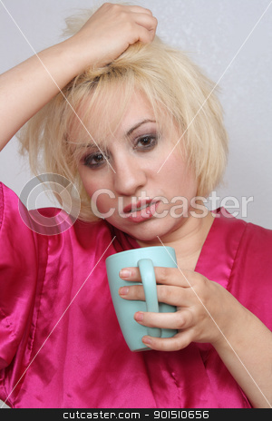 Grumpy Blonde Drinking Coffee (2) stock photo, A disheveled blonde with a grouchy facial expression, wearing a bathrobe, holds a cup of coffee. by Carl Stewart