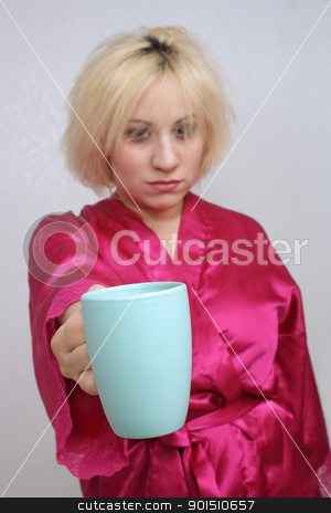 Grumpy Blonde Holds Out Her Coffee Cup stock photo, A disheveled blonde with a grouchy facial expression, wearing a bathrobe, extends a coffee cup.  Selective focus on the cup. by Carl Stewart