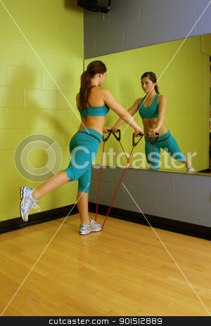 Beautiful Woman with Resistance Band (1) stock photo, A lovely young brunette with exceptional muscle tone works out with resistance bands in front of a mirror. by Carl Stewart