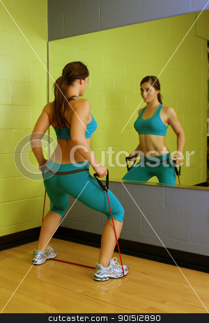 Beautiful Woman with Resistance Band (2) stock photo, A lovely young brunette with exceptional muscle tone works out with resistance bands in front of a mirror. by Carl Stewart