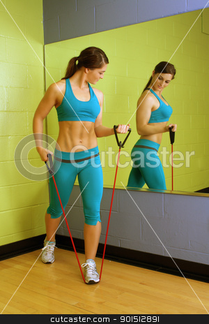 Beautiful Woman with Resistance Band (3) stock photo, A lovely young brunette with exceptional muscle tone works out with resistance bands in front of a mirror. by Carl Stewart