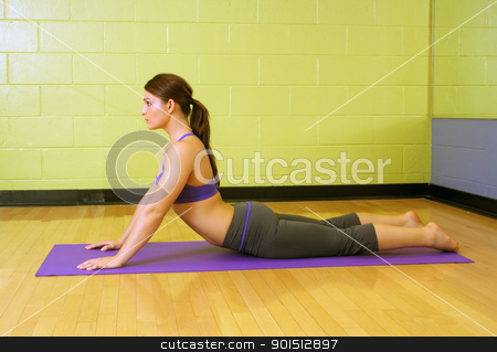 Beautiful Female Athlete at a Gym (4) stock photo, A lovely young, athletic brunette stretches on a mat at a gym. by Carl Stewart