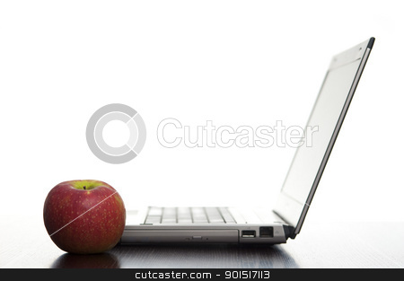 Laptop With Apple stock photo, Open laptop sideways on with a fresh red apple in an education concept. by Stephen Gibson