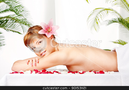 Lady with flower in hair on massage table stock photo, Pretty lady with flower in her hair relaxing on massage table by iMarin