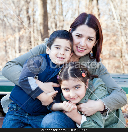 Happy Mother Hugging Her Children stock photo, Family portrait of a smiling mother hugging a boy and girl. by Dasha Rosato