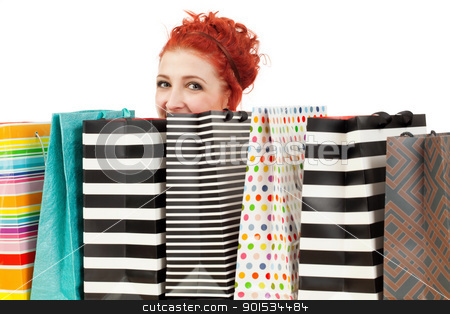 Peeking over her shopping bags stock photo, Photo of a beautiful redhead peeking over her shopping bags. by © Ron Sumners