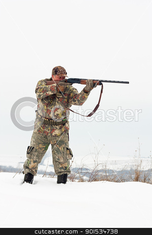 Hunter aiming stock photo, Male hunter in camouflage aiming at his target or prey with his gun.Winter scene by borojoint