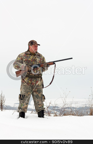 Hunter stock photo, Male hunter in camouflage,holding his gun and looking for his target or prey .Winter scene by borojoint