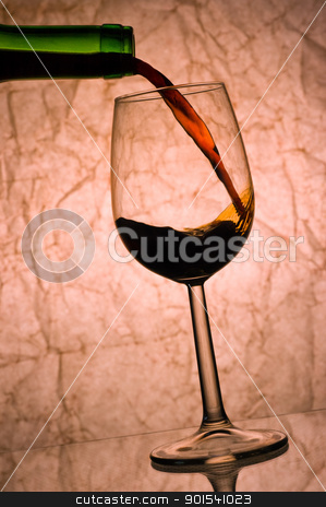 red wine pouring. stock photo, red wine pouring into glass with reflection. by Pablo Caridad