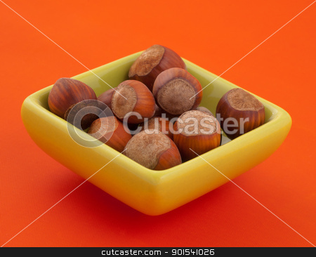 Group of hazelnuts in a bowl. stock photo, Group of hazelnuts in a bowl, with orange background and copy space. by Pablo Caridad