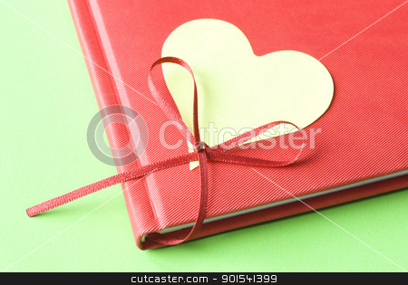 Blank Heart with Diary stock photo, Heart shaped sticky note attached to red diary on a green background. Love concept. by Tiramisu Studio