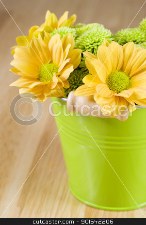 Bunch of flowers stock photo, Bunch of flowers arranged in green bucket by Tiramisu Studio