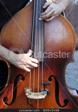 Bass stock photo, Hands playing a brown wooden bass by Henrik Lehnerer