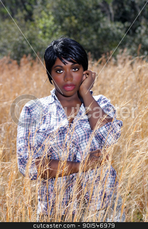 Beautiful Young Woman in Tall Grass (4) stock photo, Close-up of a lovely young woman standing in tall grass. by Carl Stewart