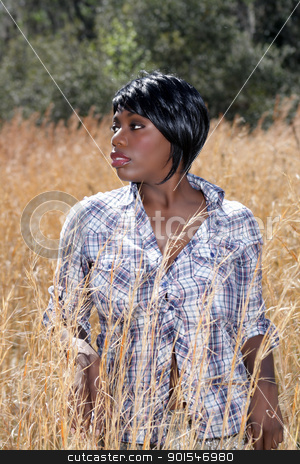 Beautiful Young Woman in Tall Grass (5) stock photo, Close-up of a lovely young woman standing in tall grass. by Carl Stewart