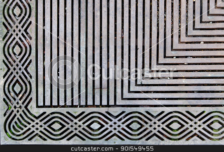 Ornate steel grate stock photo, Corner of an ornately designed steek grating on the sidewalk by bobkeenan