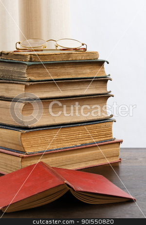 Antique Books stock photo, A stack of aged antique books with eyeglasses on top and an open red hardcover book in the foreground. by Karen Sarraga