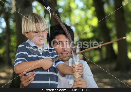 a man and a little boy doing archery in the forest stock photo, a man and a little boy doing archery in the forest by photography33