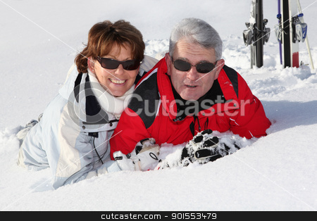 Older couple lying in the snow stock photo, Older couple lying in the snow by photography33