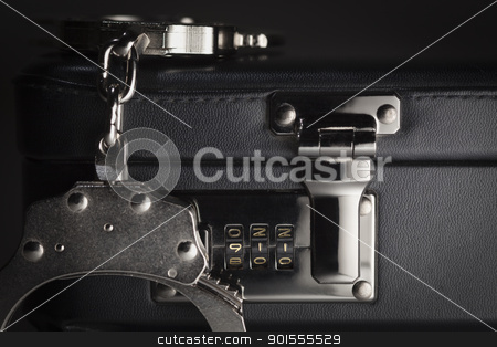Pair of Handcuffs on Briefcase with 911 on Lock stock photo, Pair of Handcuffs on Briefcase with the Numbers 911 on Lock. by Andy Dean