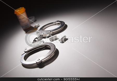 Handcuffs, Medicine Bottle and Pills Under Spot Light stock photo, Handcuffs, Medicine Bottle and Pills Under Spot Light Abstract. by Andy Dean