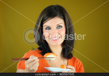 Beautiful woman eating sushi with chopsticks stock photo, Beautiful woman eating sushi with chopsticks by photography33