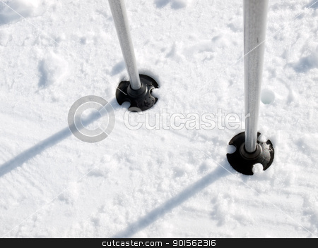 Ski poles stock photo, Closeup view on the lower part of the ski poles in the snow. by Sinisa Botas