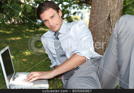 Man using a laptop in the park stock photo, Man using a laptop in the park by photography33
