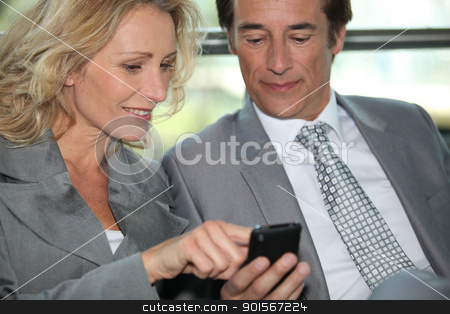 Pair of executives looking at something on a cellphone stock photo, Pair of executives looking at something on a cellphone by photography33