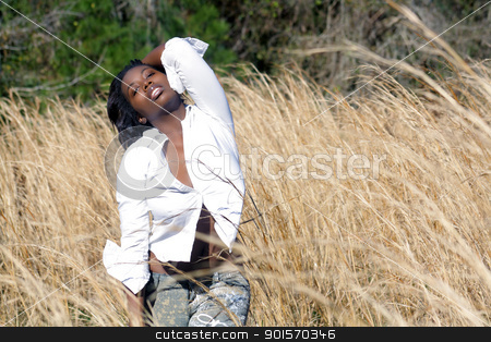 Beautiful Woman Outdoors in Tall Grass (11) stock photo, A lovely young black woman outdoors, standing in tall grass.  Generous copyspace on frame right. by Carl Stewart