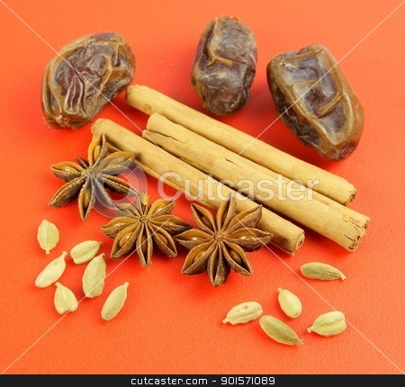 Winter flavors: Cardamom, Cinnamon, star anise, dates on red background stock photo, Four spices representing a cosy winter evening baking session. Pods of green Cardamom and fruits of star anise are placed in front of Cinnamon sticks and Medjoul dates on a warm red sheet.