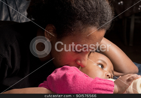 Mother and daughter stock photo, A mother and her baby girl who is drinking her bottle of milk by derejeb