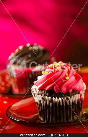 chocolate cupcakes stock photo, red and brown cupcakes on red background by Mircea Savu