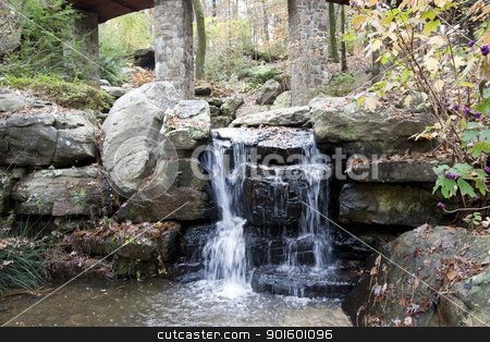 Small Waterfall stock photo, A hidden waterfall in a forest of trees by Kevin Tietz