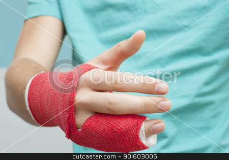 Shaking Bandaged Hand stock photo, Injured male hand with upper part of body. Hand is bandaged with red plaster focus set on thumb by KonArt