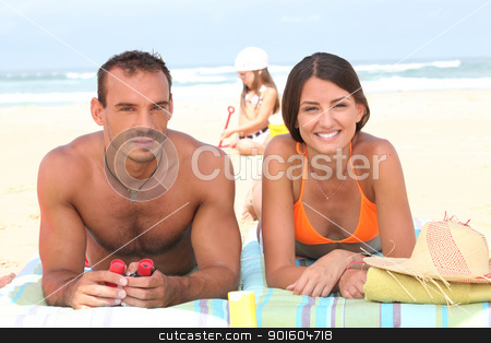 Parents sunbathing as their daughter plays in the sand behind them stock photo, Parents sunbathing as their daughter plays in the sand behind them by photography33