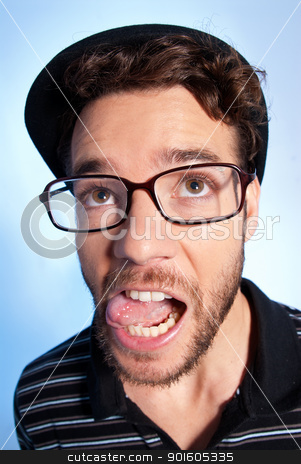 Young man modern nerd wide angle portrait blue background stock photo, Young man modern nerd with hat and glasses wide angle close up portrait on blue background by Daniel Garcia Mata