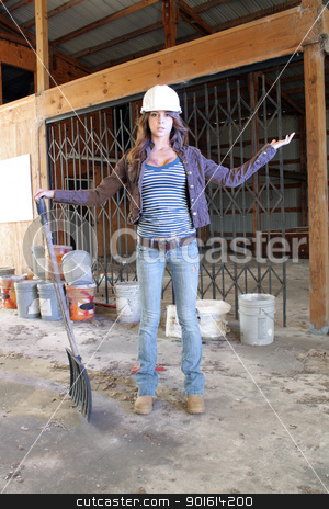Beautiful Young Construction Worker (1) stock photo, A lovely young brunette wearing a hardhat with workboots, holding a plastic shovel, stands amidst the clutter of a long-abandoned warehouse. by Carl Stewart