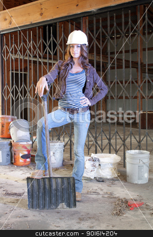 Beautiful Young Construction Worker (3) stock photo, A lovely young brunette wearing a hardhat with workboots, holding a plastic shovel, stands amidst the clutter of a long-abandoned warehouse. by Carl Stewart
