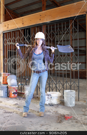 Beautiful Young Construction Worker (4) stock photo, A lovely young brunette wearing a hardhat with workboots, holding a plastic shovel, stands amidst the clutter of a long-abandoned warehouse. by Carl Stewart