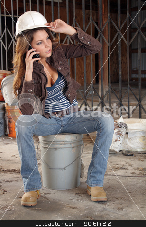 Beautiful Young Construction Worker (5) stock photo, A lovely young brunette, holding a hardhat and wearing  workboots, talks on her cell phone as she sits on a bucket amidst the clutter of a long-abandoned warehouse. by Carl Stewart