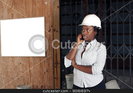 Lovely Female Construction Admin (1) stock photo, An attractive black woman wearing a white hardhat talks on her cell phone.  Beside and behind her is a white board on the wall where you can place your text or graphics. by Carl Stewart