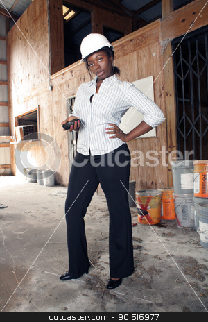 Lovely Female Construction Admin (4) stock photo, An attractive black woman wearing a white hardhat stands with her cell phone in her hand. by Carl Stewart