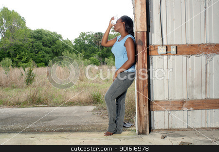Pretty Casual Woman with Bottled Water (1) stock photo, A lovely young black woman in casual wear cools off with a bottle of water. by Carl Stewart