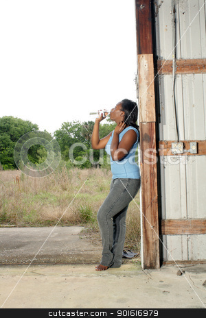Pretty Casual Woman with Bottled Water (2) stock photo, A lovely young black woman in casual wear cools off with a bottle of water. by Carl Stewart