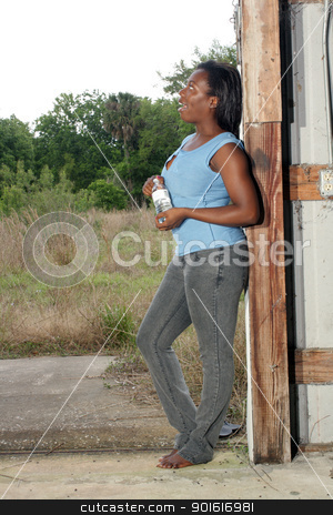 Pretty Casual Woman with Bottled Water (4) stock photo, A lovely young black woman in casual wear cools off with a bottle of water. by Carl Stewart