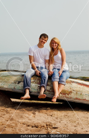 couple on a beach sitting on old boat stock photo, beautiful couple on a beach sitting on old boat by Petr Malyshev